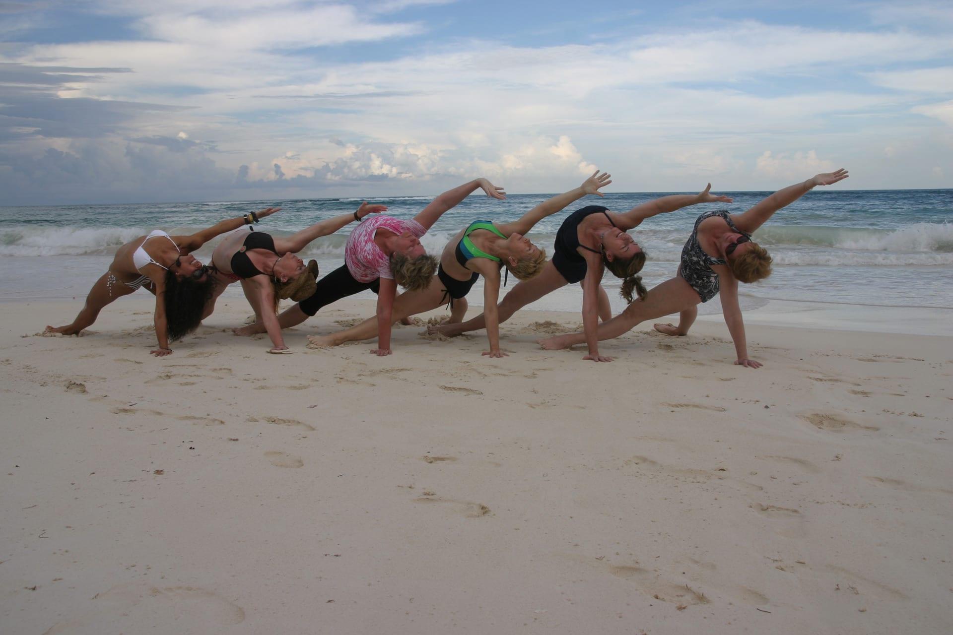 Group yoga on the beach in tulum